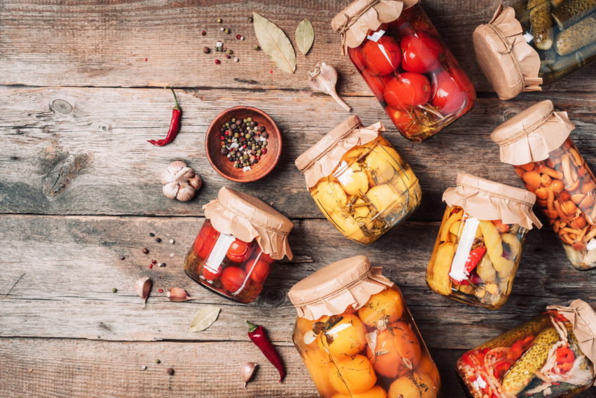 Canned And Preserved Vegetables In Glass Jars Over Wooden Background. Top View. Flat Lay. Copy Space.